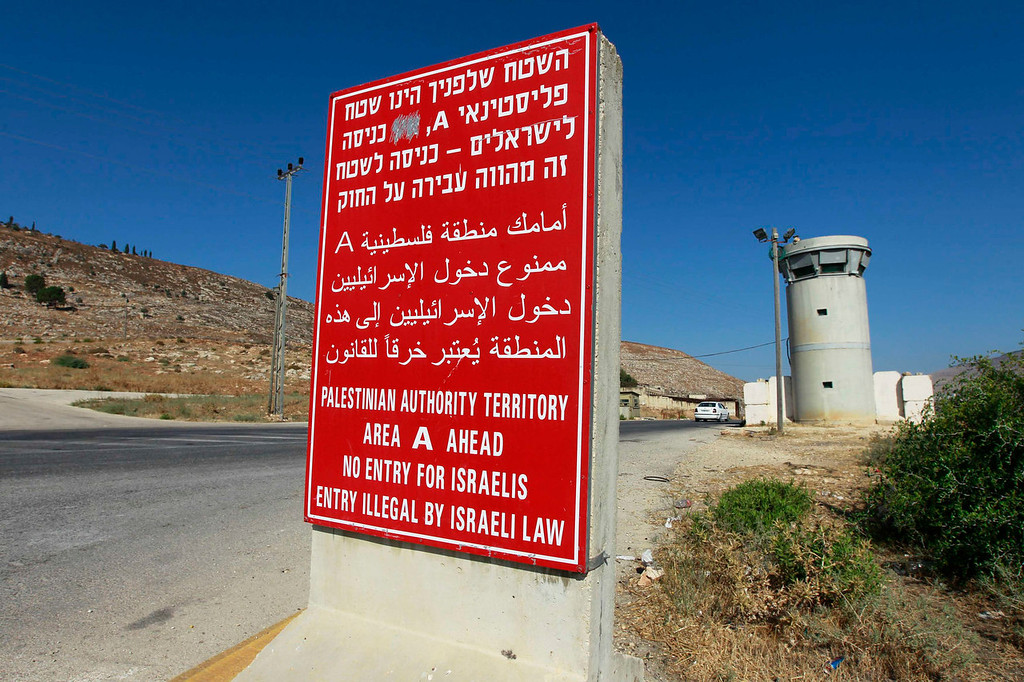 . A sign stands at an Israeli checkpoint near the West Bank city of Nablus July 23, 2013. Israeli and Palestinian officials put forward clashing formats for peace talks due to resume in Washington on Monday for the first time in nearly three years after intense U.S. mediation. It is unclear how the United States hopes to bridge the core issues in the dispute, including borders, the future of Jewish settlements on the West Bank, the fate of Palestinian refugees and the status of Jerusalem. Picture taken July 23, 2013.  REUTERS/Baz Ratner
