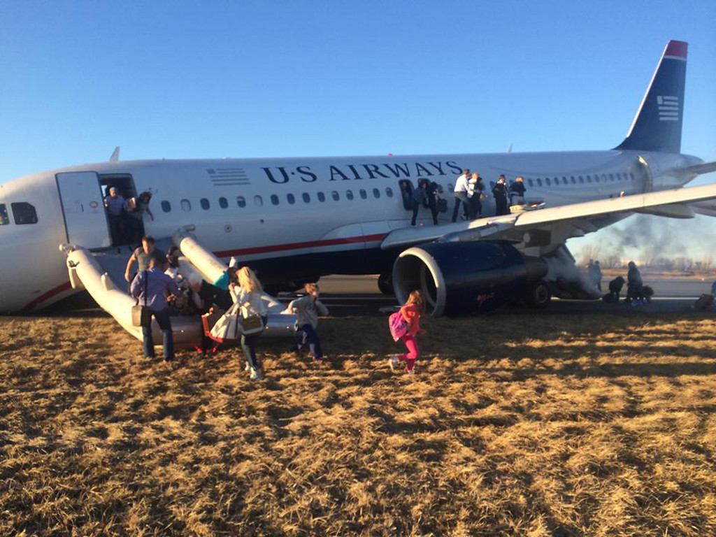 . Passengers evacuate US Airways Flight 1702 after the pilot was forced to abort takeoff shortly after 6 p.m., after a tire on the plane\'s front landing gear blew out, Thursday, March 13, 2014, in Philadelphia. The Airbus A320 jet, bound for Fort Lauderdale, Fla., was carrying 149 passengers and five crew members, airport spokeswoman Victoria Lupica said. All were rescheduled on departing flights Thursday night, she said. (AP Photo/Dennis Fee)