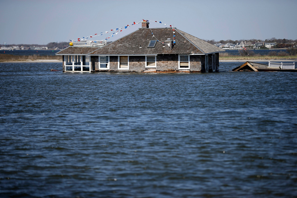 . A home rests in Barnegat Bay, Thursday, April 25, 2013, in Mantoloking, N.J., after it was swept away last October by Superstorm Sandy. Six months after Sandy devastated the Jersey shore and New York City and pounded coastal areas of New England, the region is dealing with a slow and frustrating, yet often hopeful, recovery. (AP Photo/Mel Evans)