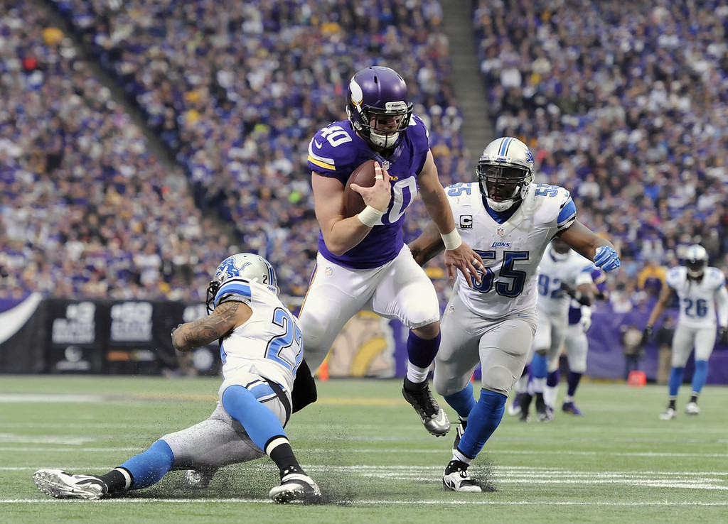 . Rhett Ellison #40 of the Minnesota Vikings carries the ball against Glover Quin #27 and Stephen Tulloch #55 of the Detroit Lions during the second quarter of the game on December 29, 2013 at Mall of America Field at the Hubert H. Humphrey Metrodome in Minneapolis, Minnesota. Ellison was injured on the play. (Photo by Hannah Foslien/Getty Images)
