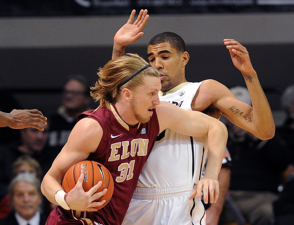 . Lucas Troutman of Elon, tries to muscle Josh Scott of CU during the first half of the December 13, 2013 game in Boulder. (Cliff Grassmick/Boulder Daily Camera)