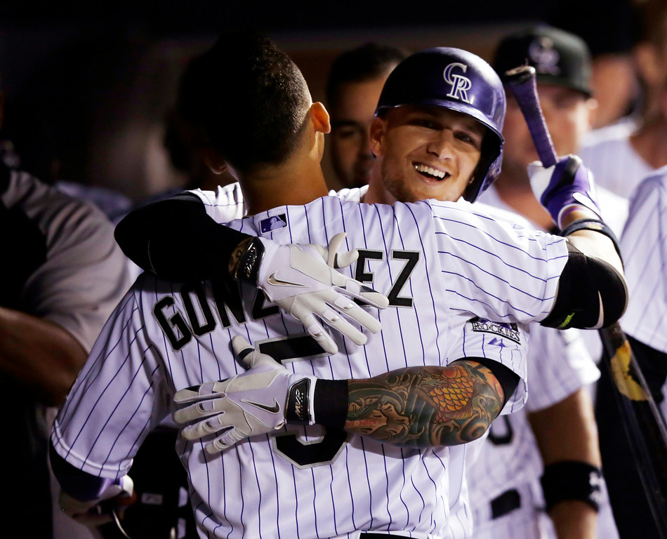 . Colorado Rockies\' Brandon Barnes hugs teammate Carlos Gonzalez (5) after hitting a solo home run against the Minnesota Twins during the seventh inning of a baseball game on Friday, July 11, 2014, in Denver. (AP Photo/Jack Dempsey)