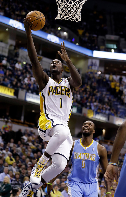 . Indiana Pacers guard Lance Stephenson, left, gets a basket in front of Denver Nuggets forward Jordan Hamilton in the second half of an NBA basketball game in Indianapolis, Monday, Feb. 10, 2014. The Pacers won 119-80.  (AP Photo/Michael Conroy)