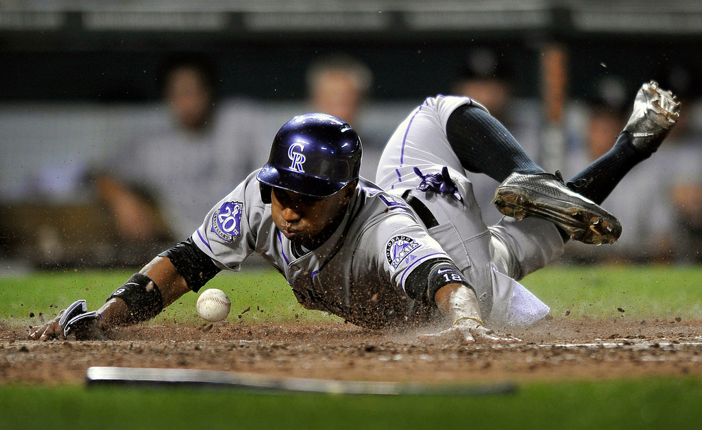 . Colorado Rockies Jonathan Herrera slides safely into home on a double by Dexter Fowler in the sixth inning of a baseball game against the Baltimore Orioles, Saturday, Aug. 17, 2013, in Baltimore. Herrera was safe on the play. (AP Photo/Gail Burton)