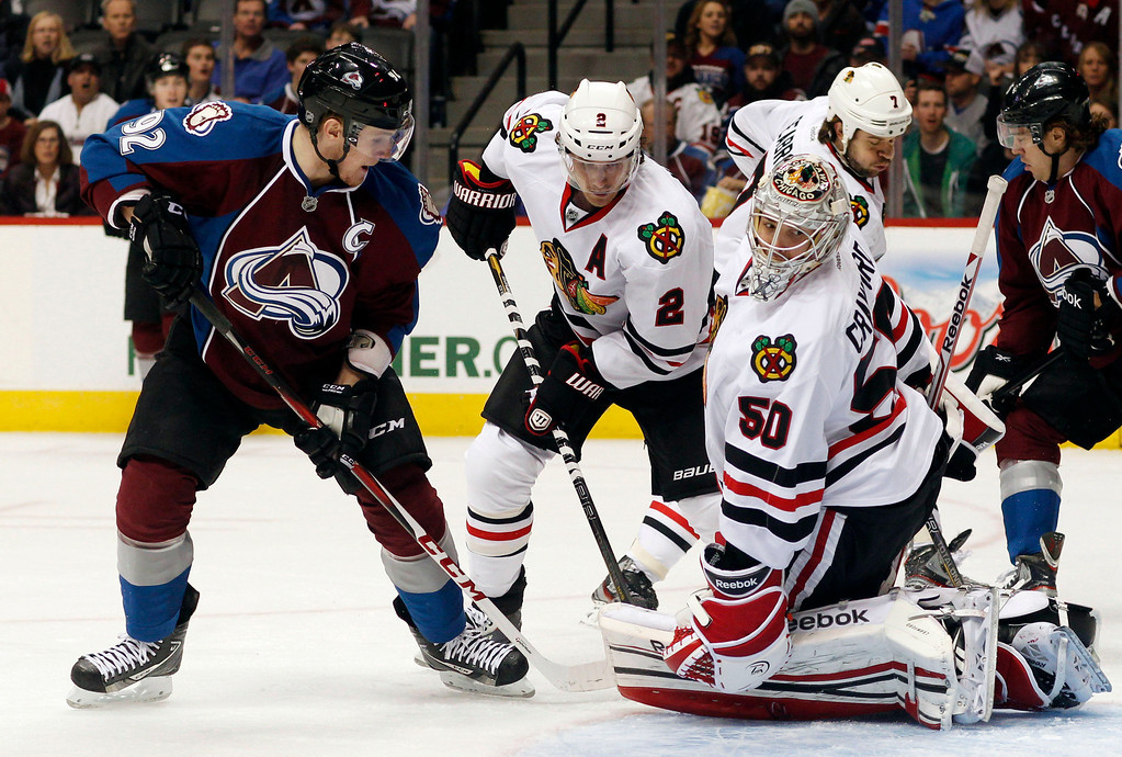 . Colorado Avalanche left wing Gabriel Landeskog, left, of Sweden, directs a shot at Chicago Blackhawks goalie Corey Crawford, right, as defenseman Duncan Keith looks on in the first period of an NHL hockey game in Denver, Friday, March 8, 2013. (AP Photo/David Zalubowski)