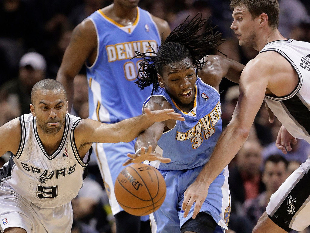 . Denver Nuggets\' Kenneth Faried (35) reaches for the ball between San Antonio Spurs\' Tony Parker (9) and Tiago Splitter, right, during the second half of an NBA basketball game, Wednesday, March 26, 2014, in San Antonio. San Antonio won 108-103. (AP Photo/Eric Gay)