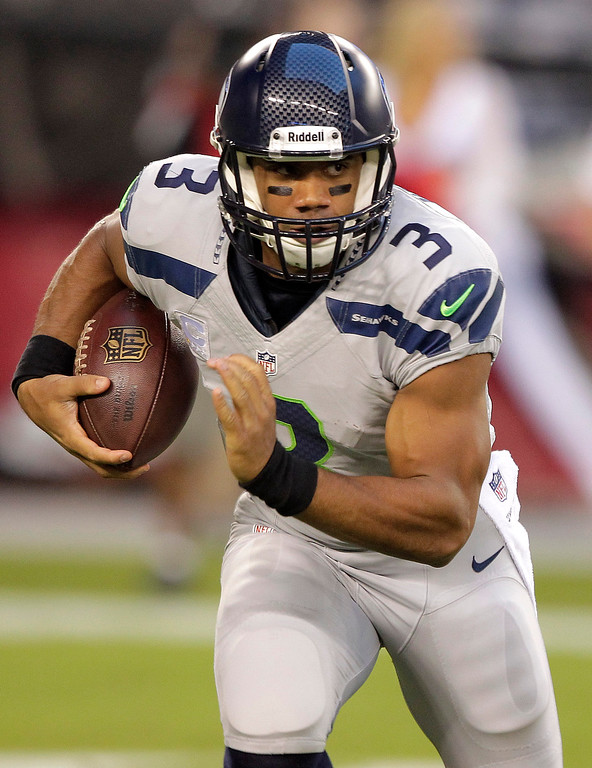 . Seattle Seahawks quarterback Russell Wilson runs against the Arizona Cardinals during the first half of an NFL football game, Thursday, Oct. 17, 2013, in Glendale, Ariz. (AP Photo/Rick Scuteri)