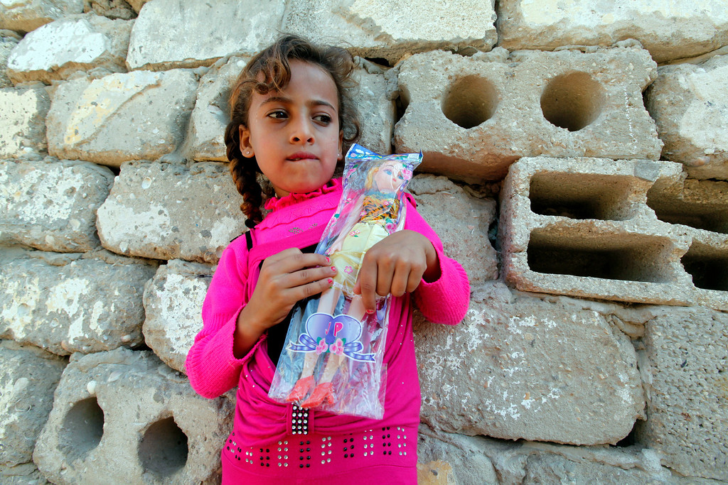 . In this Thursday, Oct. 17, 2013 photo, Heba Alwadiya, 6, holds a toy she received from her grandfather Salih Alwadiya, a tradition for the Muslim festival of Eid al-Adha, in front of their family house in Gaza City. Salih Alwadiya, 61, the patriarch of the extended family has 20 children, from three wives, most of whom live with him in a small makeshift warren of shacks near a sewage plant. (AP Photo/Adel Hana)