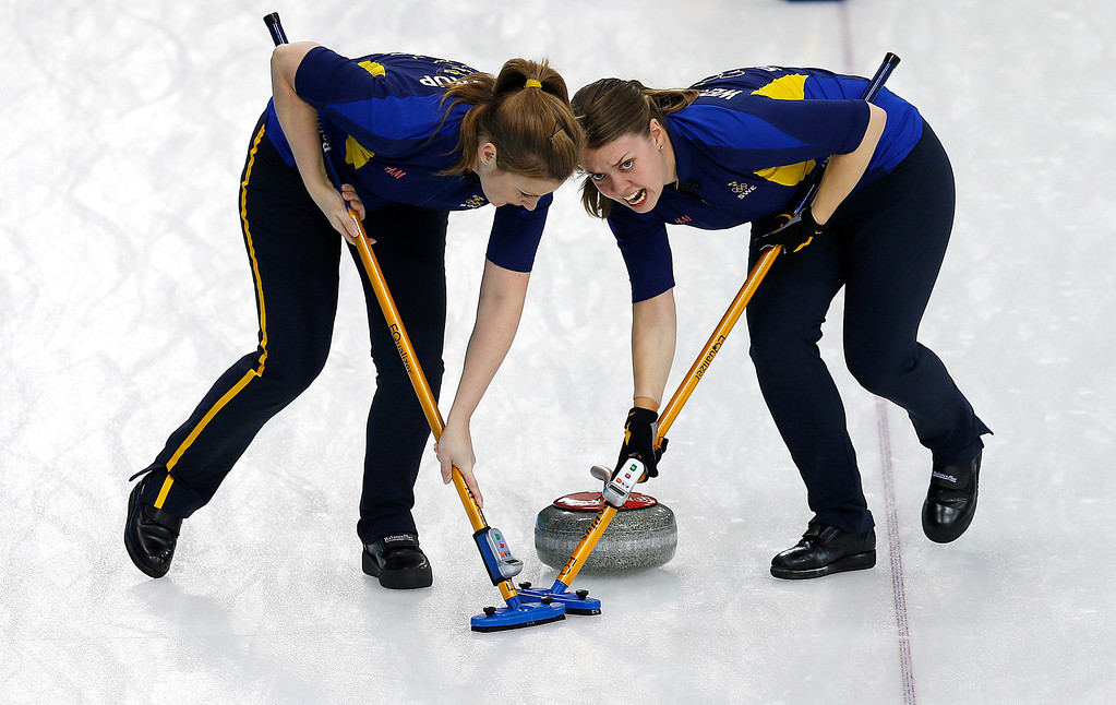 . Sweden\'s Maria Wennerstroem, right and Christina Bertrup, left, sweep the ice during the women\'s curling competition against Denmark at the 2014 Winter Olympics, Thursday, Feb. 13, 2014, in Sochi, Russia. (AP Photo/Wong Maye-E)