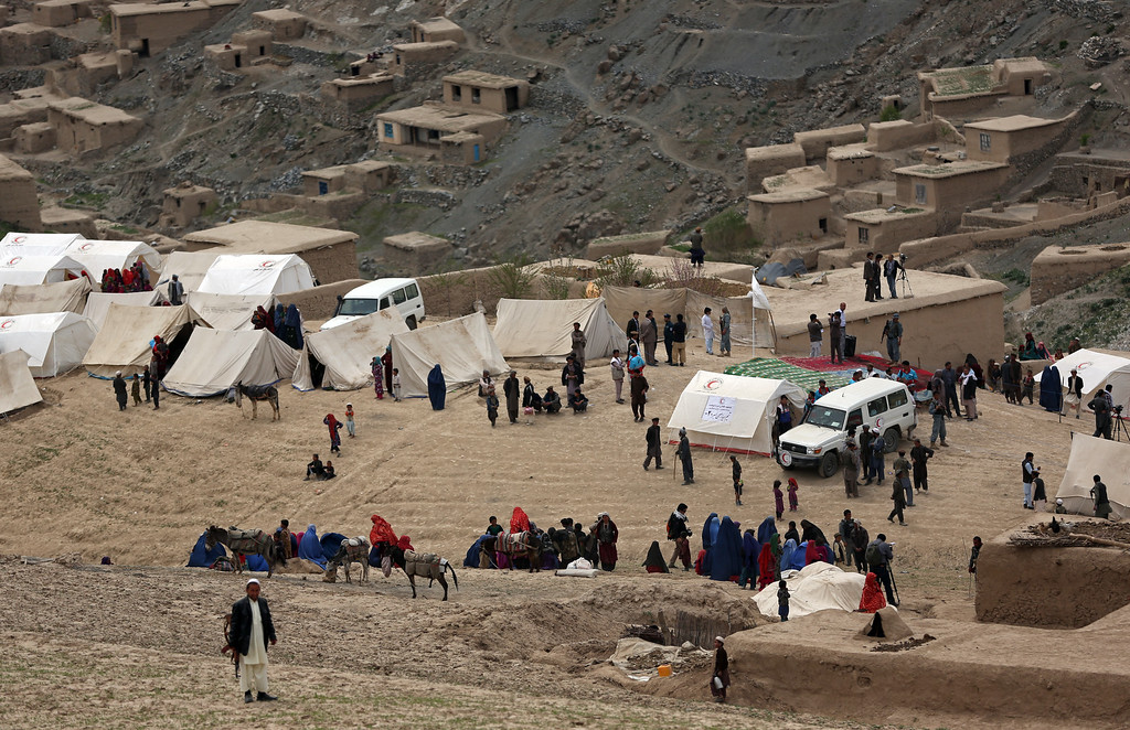 . In this Sunday, May 4, 2014 photo, Survivors sit with their possessions near the site of Friday\'s landslide that buried Abi-Barik village in Badakhshan province, northeastern Afghanistan.  (AP Photo/Massoud Hossaini)