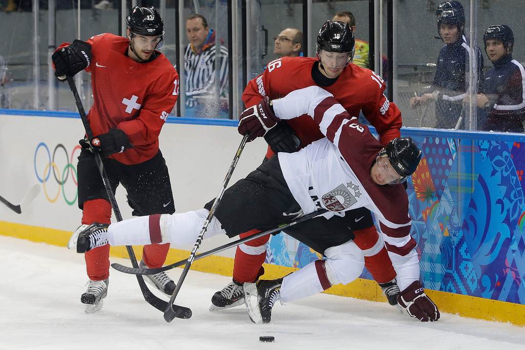 . Latvia forward Juris Stals hits the ice in front of Switzerland forward Luca Cunti and defenseman Raphael Diaz during the second period in the 2014 Winter Olympics men\'s ice hockey game at Shayba Arena, Wednesday, Feb. 12, 2014, in Sochi, Russia. (AP Photo/Matt Slocum)