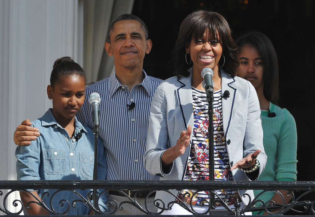 . US First Lady Michelle Obama speaks watched by (from left) Sasha, US President Barack Obama, and daughter Malia at the start of the annual Easter Egg Roll on April 1, 2013 at the White House in Washington, DC. AFP PHOTO/Mandel NGAN/AFP/Getty Images