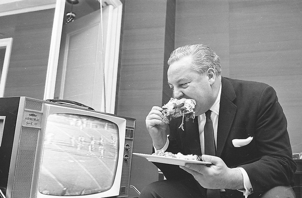 . Sports announcer and founder of the American Football League Harry Wismer eats a Thanksgiving snack in his New York hotel room, Nov. 22, 1962, while watching his team, the New York Titans, edge the Denver Broncos, 46-45 on television. (AP Photo/Marty Lederhandler)