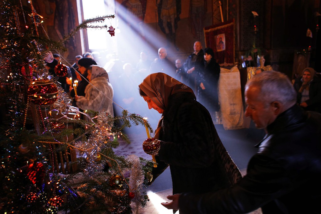 . A Romanian woman, holding a burning candle, attends the Christmas mass in the Orthodox church of Malaia village, 250 km north-west from Bucharest, Romania, 25 December 2013.  EPA/ROBERT GHEMENT