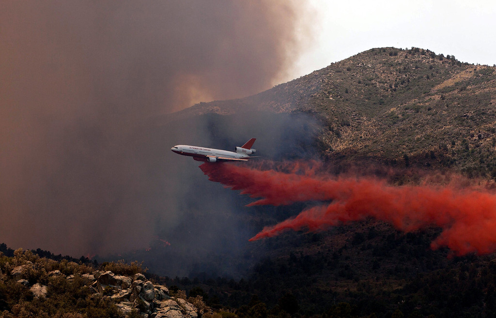 . Tanker 910 makes a retardant drop on the Yarnell Hill Fire to help protect the Double Bar A Ranch near Peeples Valley, Ariz., Sunday, June 30, 2013. The fire started Friday and picked up momentum as the area experienced high temperatures, low humidity and windy conditions. It has forced the evacuation of residents in the Peeples Valley area and in the town of Yarnell. (AP Photo/The Arizona Republic, Tom Story)
