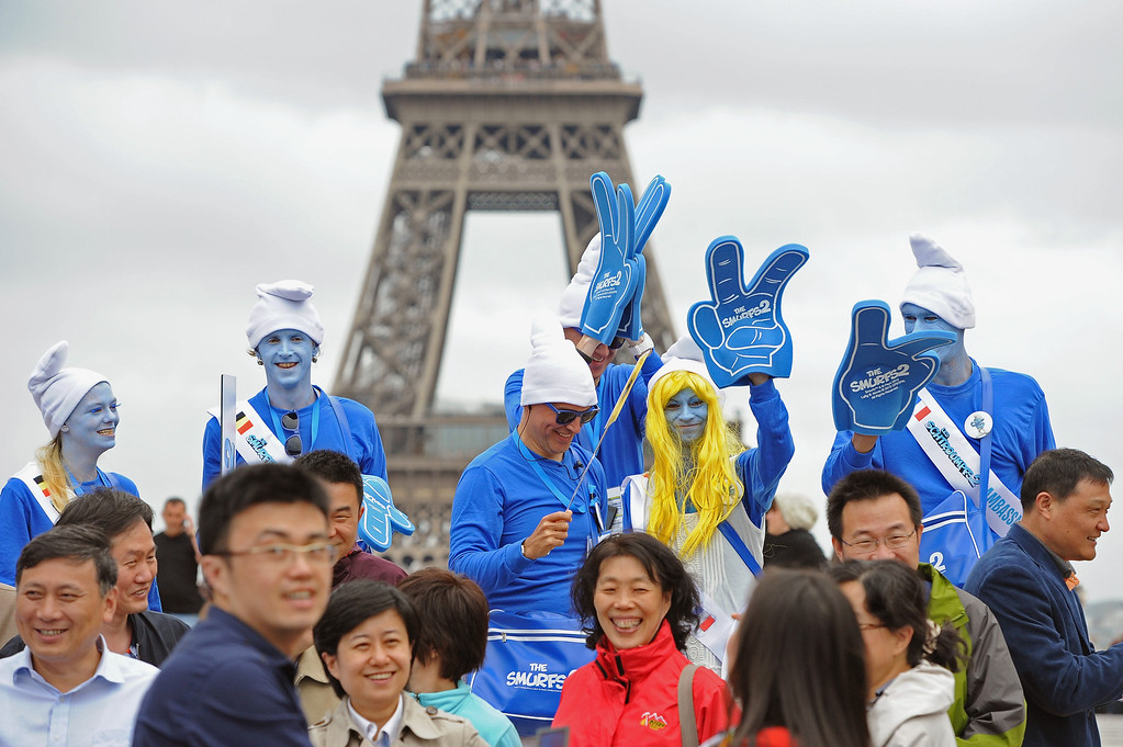 . A group of tourists mixes with Smurf Ambassadors as they pose for a group photo on the Trocadero plaza as part of Global Smurfs Day celebrations on June 22, 2013 in Paris, France. The Eiffel tower is seen behind.  (Photo by Pascal Le Segretain/Getty Images for Sony Pictures Entertainment)