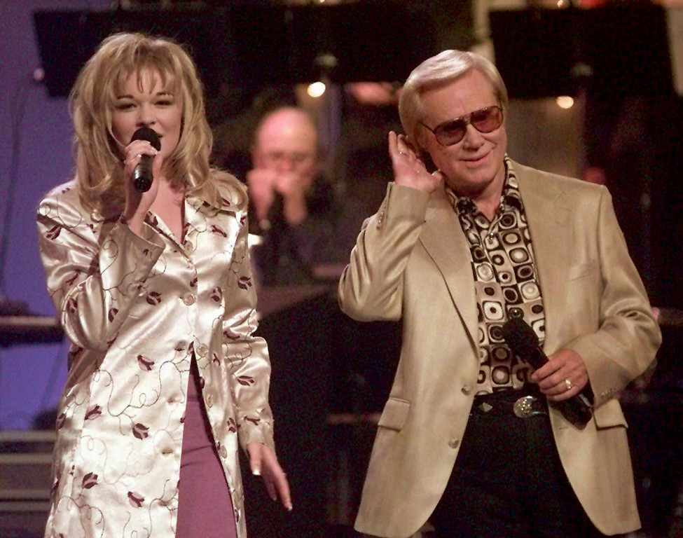 ". In this June 16, 1997 file photo, Country music veteran George Jones bends an ear toward 14-year-old newcomer LeAnn Rimes during the opening segment of the TNN-Music City News Country Awards show in Nashville, Tenn.,  Jones, the peerless, hard-living country singer who recorded dozens of hits about good times and regrets and peaked with the heartbreaking classic ""He Stopped Loving Her Today,\"" has died. He was 81. Jones died Friday, April 26, 2013 at Vanderbilt University Medical Center in Nashville after being hospitalized with fever and irregular blood pressure, according to his publicist Kirt Webster. (AP Photo/Mark Humphrey, file)"
