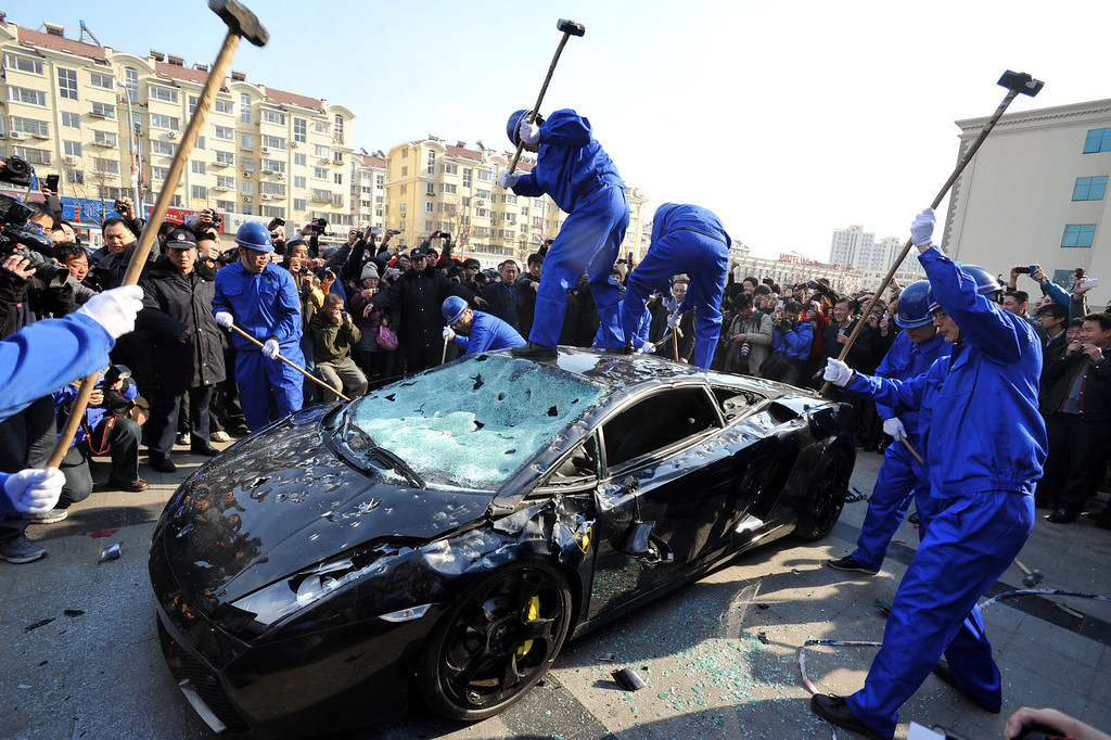 . Workers destroy a Lamborghini Gallardo L140 luxury sports car to mark World Consumer Rights Day in Qingdao, eastern China\'s Shandong province on March 15, 2011. The car\'s owner hired people to publicly destroy the vehicle when it failed to function after a service by an official Lamborghini service station. The protest was made to provoke public support and goad the manufacturer to respect his consumer rights. AFP/Getty Images