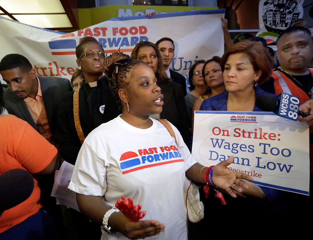 . Shaniqua Davis, center, who works at a McDonald\'s earning $7.25 an hour, speaks at a fast food workers\' protest outside a McDonald\'s restaurant on New York\'s Fifth Avenue, Thursday, Aug. 29, 2013. (AP Photo/Richard Drew)