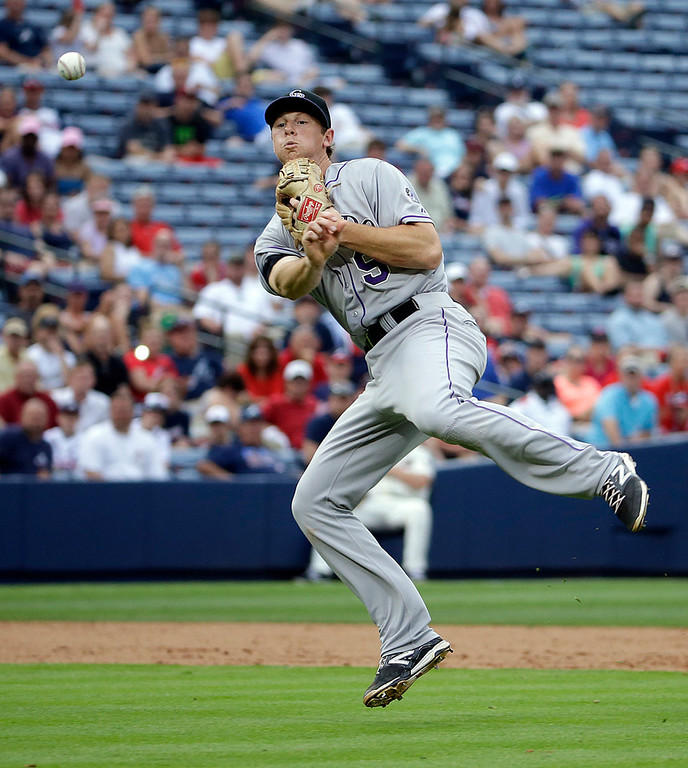 . Colorado Rockies DJ LeMahieu throws to first base after fielding a ground out by Atlanta Braves\' Chris Johnson in the ninth inning of a baseball game, Saturday, May 24, 2014, in Atlanta. (AP Photo/David Goldman)