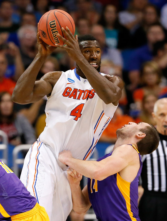 . ORLANDO, FL - MARCH 20:  Patric Young #4 of the Florida Gators charges into Sam Rowley #14 of the Albany Great Danes in the second half during the second round of the 2014 NCAA Men\'s Basketball Tournament at Amway Center on March 20, 2014 in Orlando, Florida.  (Photo by Kevin C. Cox/Getty Images)