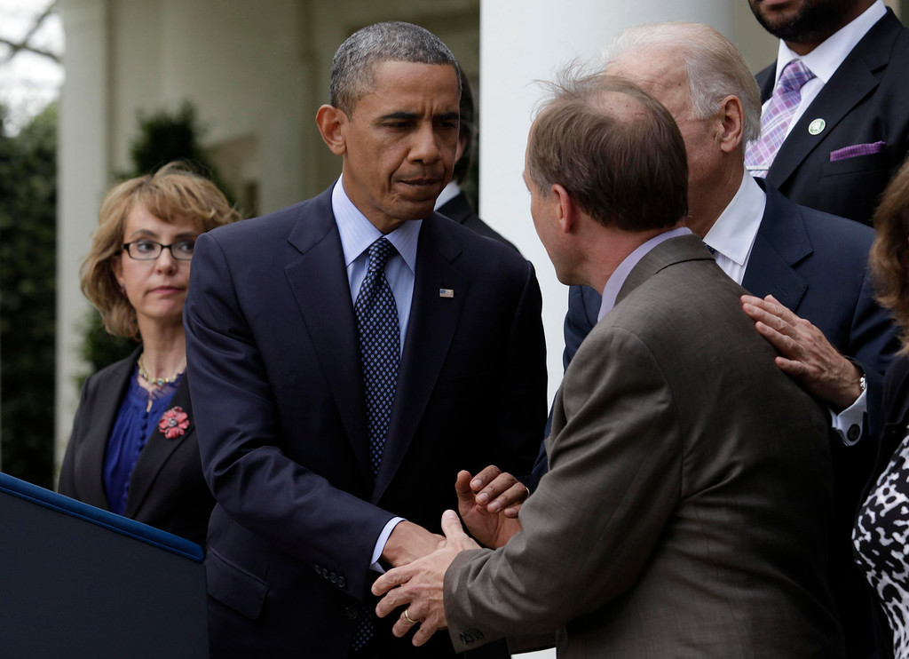. U.S. President Barack Obama shakes hands with Mark Barden, the father of Newtown shooting victim Daniel, as former Rep. Gabby Giffords (L) looks on before delivering a statement on commonsense measures to reduce gun violence in the Rose Garden of the White House in Washington,  April 17, 2013. Joined by relatives of the victims of gun violence, President Barack Obama on Wednesday angrily blamed politics for the failure of gun control legislation and urged voters to send a message at the ballot box that they want stronger gun laws. REUTERS/Yuri Gripas