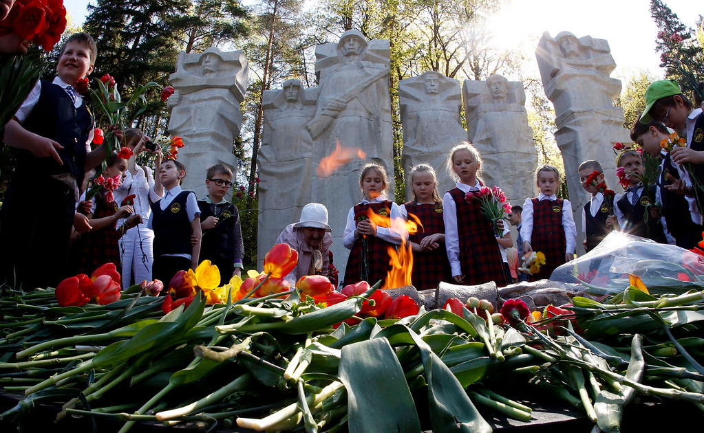 . Children lay flowers at the grave of the Unknown Soldier at the Antakalnis memorial during Victory Day celebrations in Vilnius, Lithuania, Thursday, May 9, 2013. Several nations are celebrating the anniversary of victory over Nazi Germany in WWII. (AP Photo/Mindaugas Kulbis)