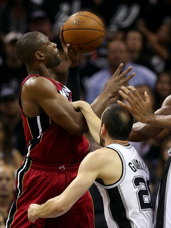 . Dwyane Wade #3 of the Miami Heat goes up for a shot as he is grabbed by Manu Ginobili #20 of the San Antonio Spurs in the second quarter during Game Three of the 2013 NBA Finals at the AT&T Center on June 11, 2013 in San Antonio, Texas.   (Photo by Mike Ehrmann/Getty Images)
