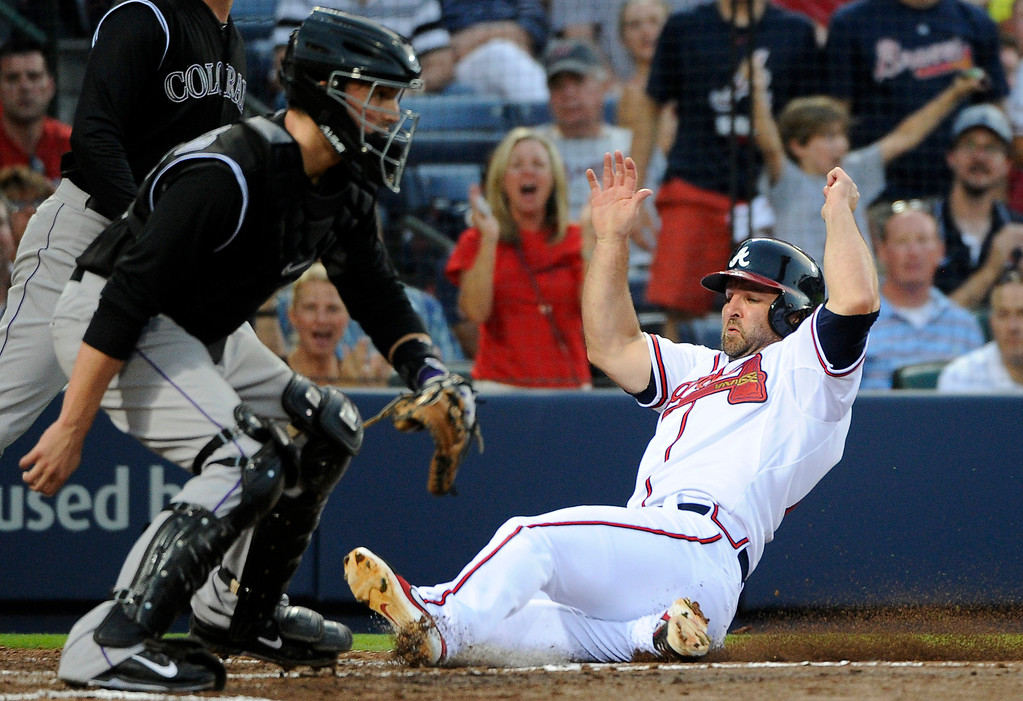 . Atlanta Braves\' Dan Uggla, right, scores ahead of the throw to Colorado Rockies catcher Jordan Pacheco on a hit by Gerald Laird during the second inning of a baseball game Friday, May 23, 2014, in Atlanta. (AP Photo/David Tulis)