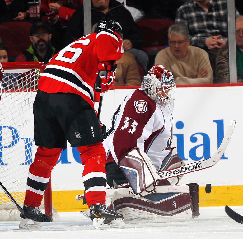 . Goalie Jean-Sebastien Giguere #35 of the Colorado Avalanche knocks the puck away from in front of Patrik Elias #26 of the New Jersey Devils during the first period of an NHL hockey game at Prudential Center on February 3, 2014 in Newark, New Jersey.  (Photo by Paul Bereswill/Getty Images)