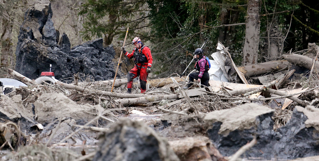 . Searchers look through debris from a deadly mudslide Tuesday, March 25, 2014, in Oso, Wash.  (AP Photo/Elaine Thompson)