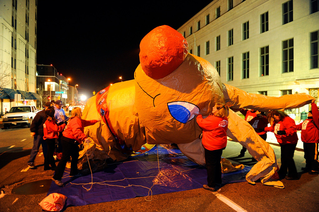 . Crew worked to inflate the Rudolph balloon with helium before the parade Friday night. The annual Parade of Lights filed past the illuminated City and County building in downtown Denver Friday night, November 30. 2012. The parade with 11 floats, 7 bands, 5 giant balloons and more lights than anyone could count, had enough holiday spirit for everyone. Karl Gehring/ The Denver Post