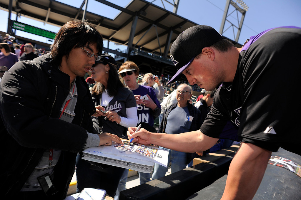 . SCOTTSDALE, AZ. - FEBRUARY 23: Colorado Rockies fan gets an autograph from Jordan Pacheco (15) of the Colorado Rockies before their game against the Arizona Diamondbacks February 23, 2013 in Scottsdale. (Photo By John Leyba/The Denver Post)