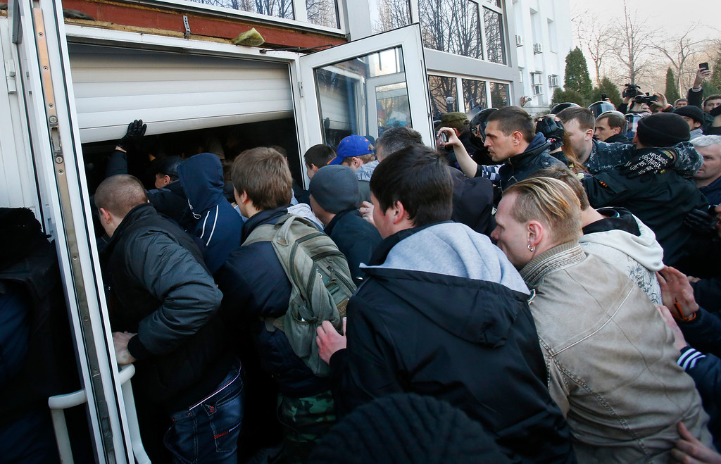 . Pro Russia protestors storm the door of the regional governance Security Service of Ukraine building during a rally in Donetsk, Ukraine, Saturday, March 15, 2014. (AP Photo/Sergei Grits)