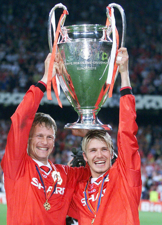 . In a file picture taken on May 26, 1999 Manchester United\'s English midfielders Teddy Sheringham (L) and David Beckham (R) hold aloft the UEFA Champions League trophy after winning the final footbal match against Bayern Munich at the Camp Nou Stadium in Barcelona.  PATRICK HERTZOG/AFP/Getty Images