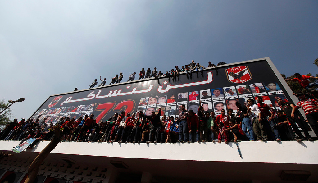 ". Al-Ahly fans, also known as ""Ultras\"", shout slogans against the Interior Ministry, in front of the Al-Ahly club after hearing the final verdict of the 2012 Port Said massacre in Cairo March 9, 2013.  The poster with pictures of fans who died in Port Said reads \""We can\'t forget you\"". REUTERS/Amr Abdallah Dalsh"