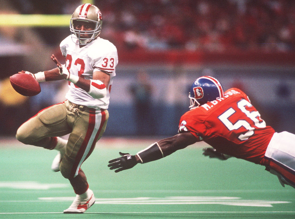 . Running BAck Roger Craig of the San Francisco 49ers evades a Broncos defender during Super Bowl XXIV in New Orleans.  (Rick Stewart/Allsport)