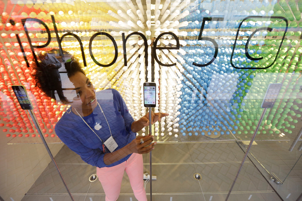 . Sales associate Mila Thomas adjusts a display of phones during the opening day of sales of the new iPhone 5s and iPhone 5C in Richmond, Va., Friday, Sept. 20, 2013. (AP Photo/Steve Helber)