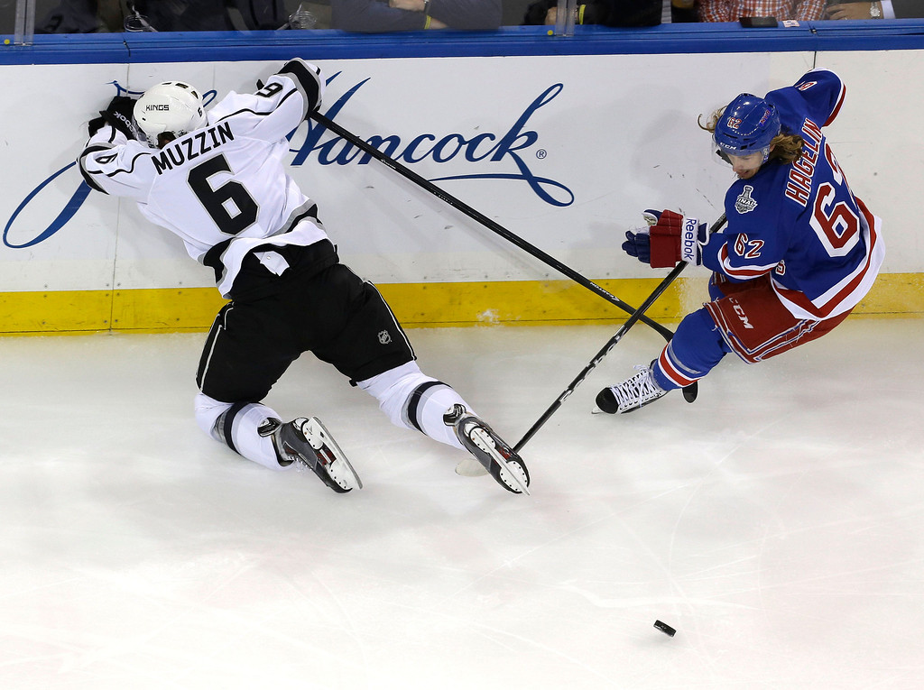 . Los Angeles Kings defenseman Jake Muzzin (6), left, hits the boards while New York Rangers left wing Carl Hagelin (62) chases the puck in the first period during Game 4 of the NHL hockey Stanley Cup Final, Wednesday, June 11, 2014, in New York. (AP Photo/Seth Wenig)