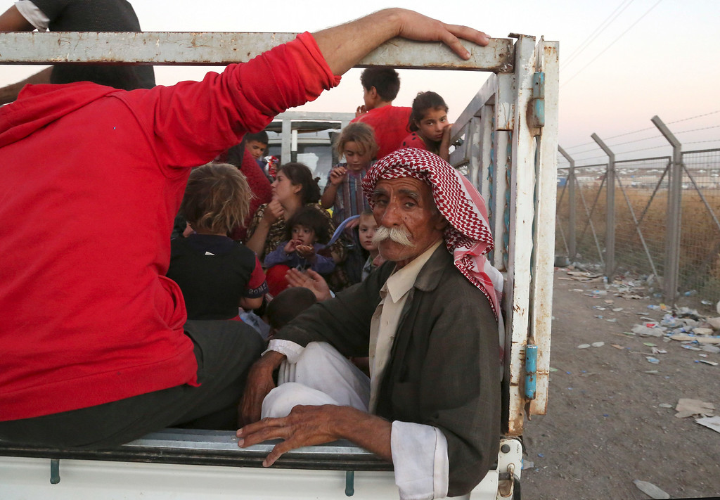 . Displaced Iraqis from the Yazidi community arrive to the camp of Bajid Kandala at Feeshkhabour town near the Syria-Iraq border, in Iraq Saturday, Aug. 9, 2014. (AP Photo/ Khalid Mohammed)