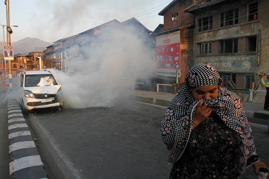 . A Kashmiri woman runs as tear gas explodes near a car that was fired upon by paramilitary troops when the driver allegedly failed to stop the car at a police barricade in Srinagar, India, Saturday, Sept. 7, 2013. A protest erupted Saturday after Indian police said they killed two alleged militants and two civilians in the disputed Himalayan territory of Kashmir, while authorities maintained tight security for a classical music concert being staged amid separatist objections. The driver was hospitalized in critical condition. (AP Photo/Mukhtar Khan)