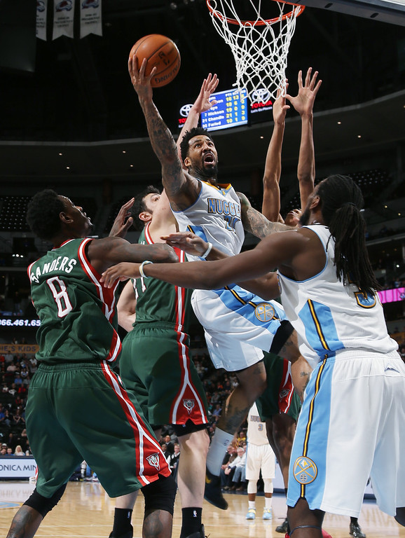 . Denver Nuggets forward Wilson Chandler drives for shot past Milwaukee Bucks center Larry Sanders, left, and forward Zaza Pachulia, of Georgia, second from left, as Nuggets forward Kenneth Faried defends during the fourth quarter of the Nuggets\' 110-100 victory in an NBA basketball game in Denver on Wednesday, Feb. 5, 2014. (AP Photo/David Zalubowski)
