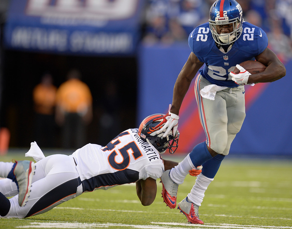 . New York Giants running back David Wilson (22) pushes Denver Broncos cornerback Dominique Rodgers-Cromartie (45) down to the ground while picking up a few yards during the second quarter September 15, 2013 MetLife Stadium. (Photo by John Leyba/The Denver Post)