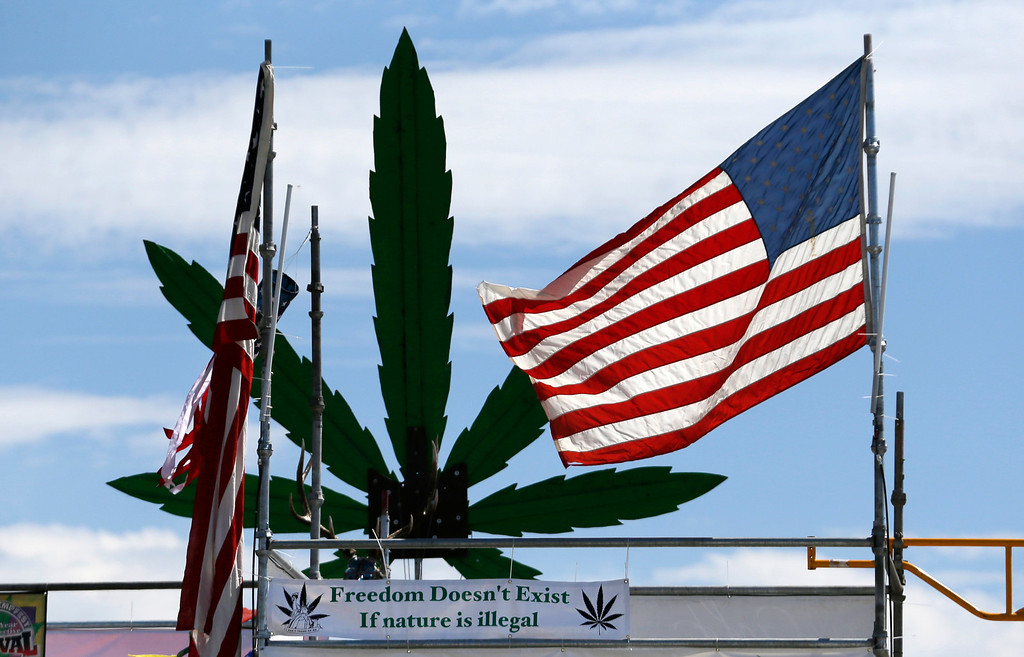 . An American flag flies atop the stage at the first day of Hempfest, Friday, Aug. 16, 2013, in Seattle. Thousands packed the Seattle waterfront park for the opening of a three-day marijuana festival � an event that is part party, part protest and part victory celebration after the legalization of pot in Washington and Colorado last fall. Hempfest was expected to draw as many as 85,000 people per day. (AP Photo/Elaine Thompson)