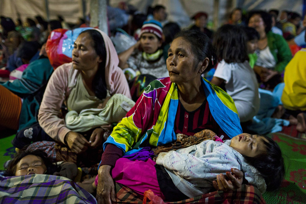 . Indonesian woman holds their baby at a temporary evacuation shelter in Berastagi village on November 25, 2013 in Karo district, North Sumatra, Indonesia. (Photo by Ulet Ifansasti/Getty Images)