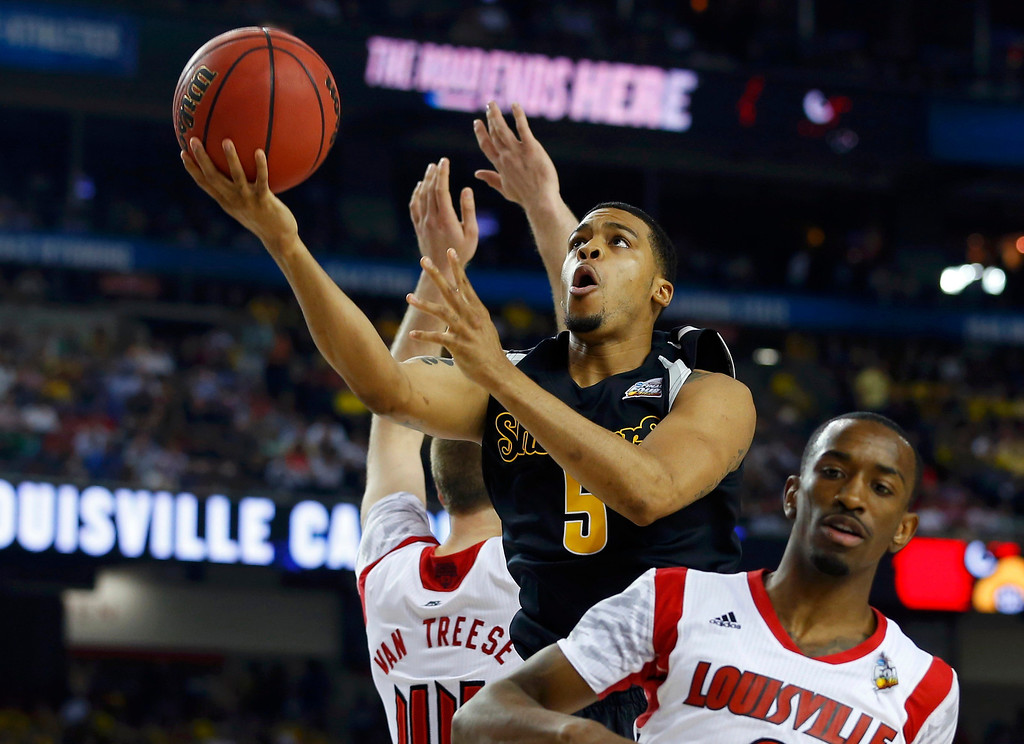 . Wichita State Shockers guard Demetric Williams (C) drives to the net between Louisville Cardinals forward Stephan Van Treese (L) and guard Russ Smith during the first half of their NCAA men\'s Final Four basketball game in Atlanta, Georgia April 6, 2013. REUTERS/Chris Keane