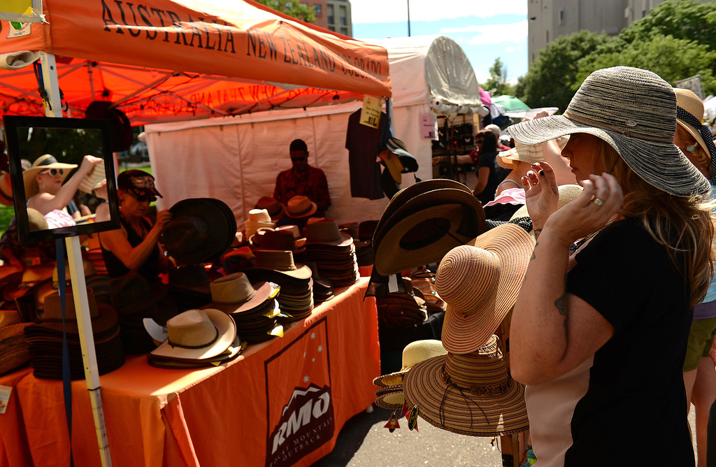 . Stacye Heaton, of Durango, tries on a variety of hats at the Rocky Mountain Outback Hats stand at the Taste of Colorado at Civic Center Park in Denver on Sunday, August 31, 2014.    (Photo By Helen H. Richardson/ The Denver Post)