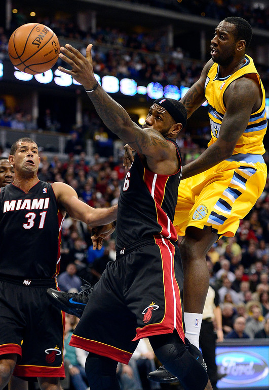 . LeBron James (6) of the Miami Heat tries to wrangle a loose ball as J.J. Hickson (7) of the Denver Nuggets defends during the first half of action.  Photo by AAron Ontiveroz/The Denver Post)