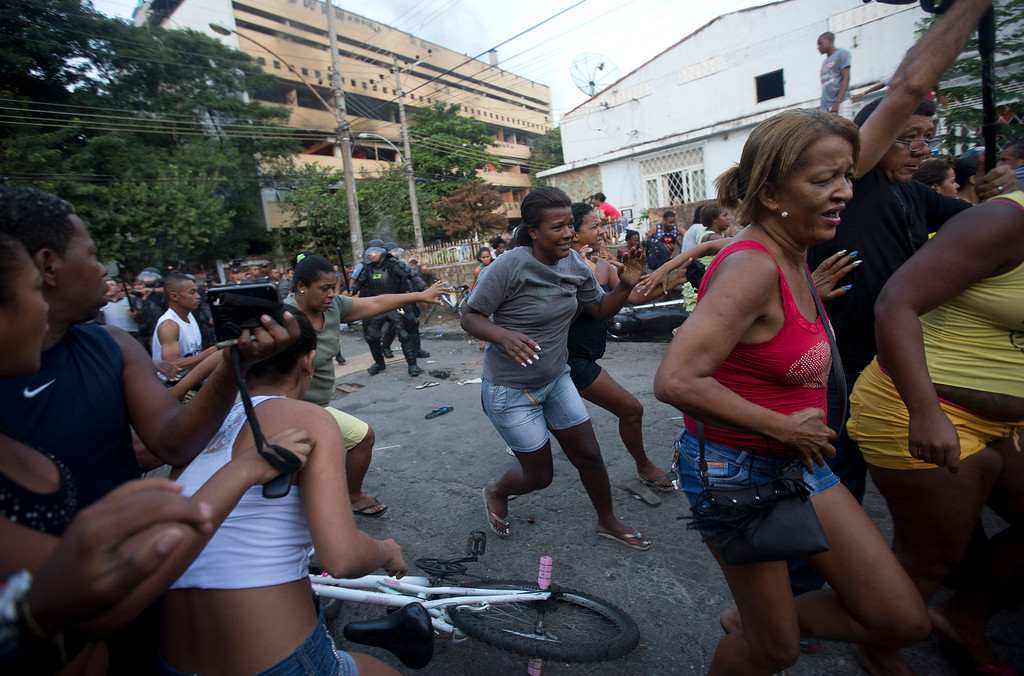 . Squatters run away from tear gas while police try to disperse them during an eviction in Rio de Janeiro, Brazil, Friday, April 11, 2014. Squatters in Rio de Janeiro are clashing with police after a Brazilian court ordered that 5,000 people be evicted from abandoned buildings of a telecommunications company. Officers have used tear gas and stun grenades to try to disperse the families. (AP Photo/Silvia Izquierdo)
