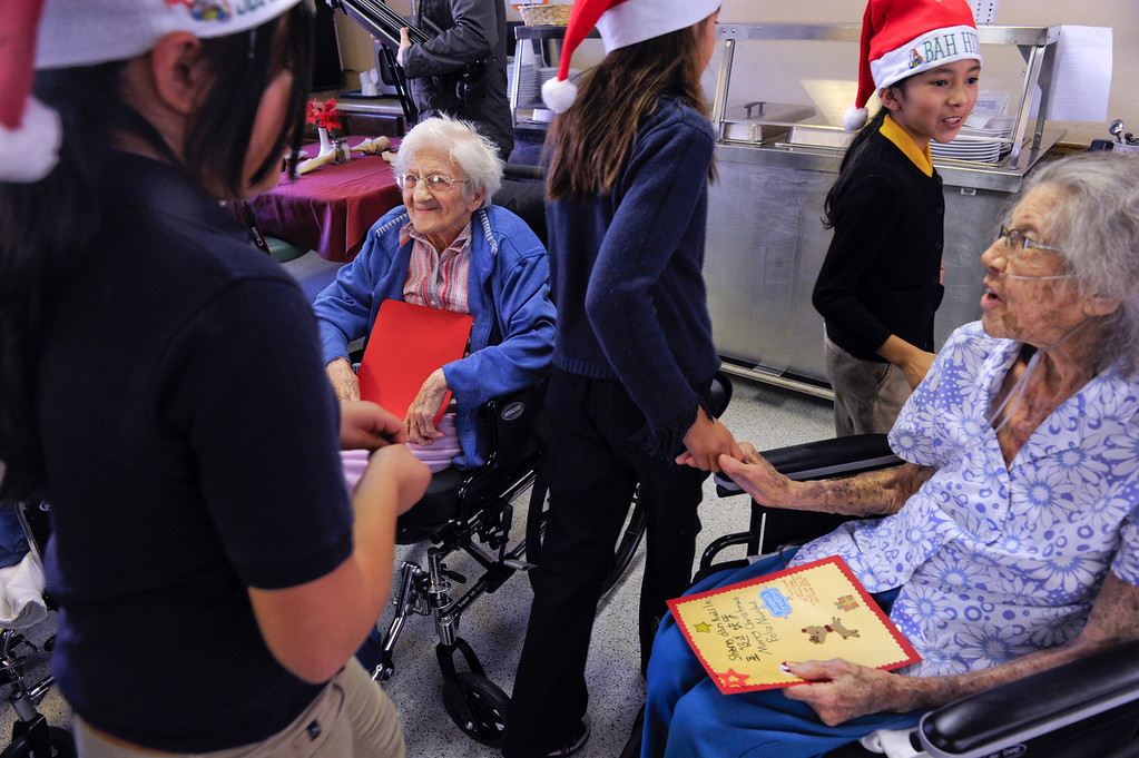 . Sophia Mehos, second from left, and Lillian Givens, right, are greeted by students and parents from the Denver Center for International Studies at Ford Elementary School as the kids spend a Saturday singing holiday songs in three different languages to the residents of the Kindred Care nursing home. (Photo by Kathryn Scott Osler/The Denver Post)